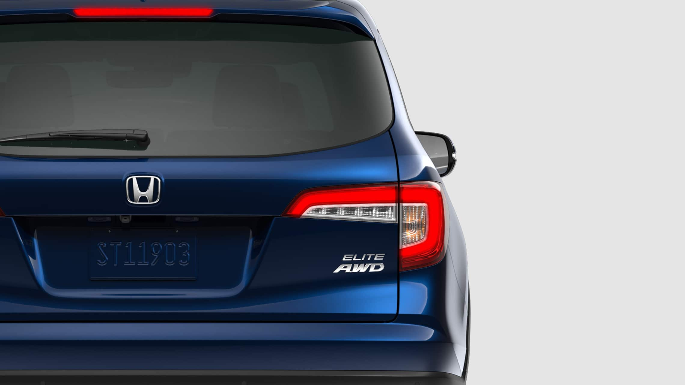 Rear driver-side close-up view of 2021 Honda Pilot Elite in Obsidian Blue Pearl.